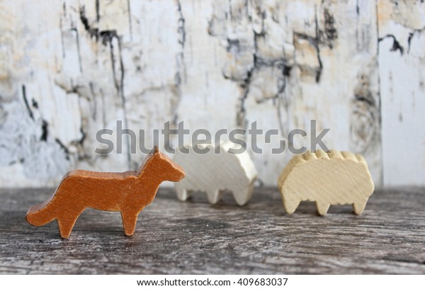 Wooden wolf and two sheep concept image, signifying a wolf in sheep's clothing idiom