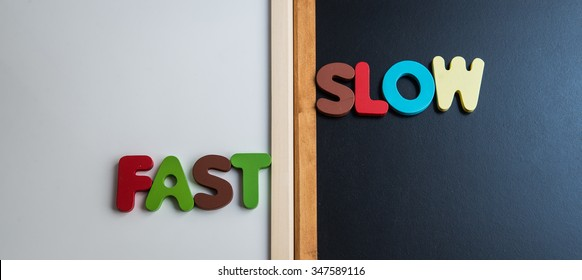 Wooden word FAST and SLOW on black board and white board