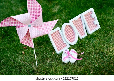 Wooden word love and little shoes in the green grass.
