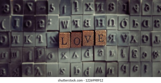 The wooden word love on the background of the elements of the font