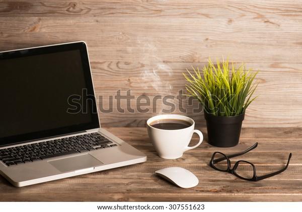 Holzarbeitsplatz mit Laptop, Tasse heißen Kaffee, Maus, Gläser und Topfpflanze, in hellen, hellen Vintage-Tönen.