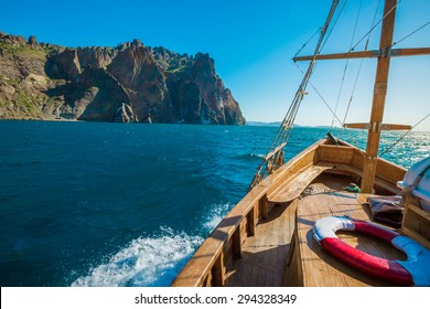 Wooden yacht. Vintage boat floating near the shore of a mountain. Fishing in the sea.