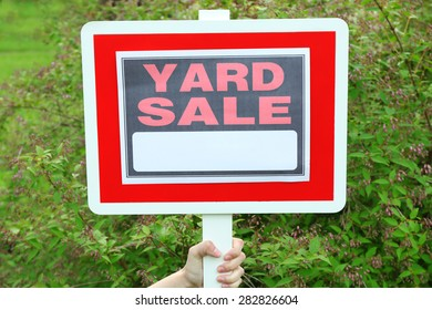 Wooden Yard Sale sign in female hand over green grass background