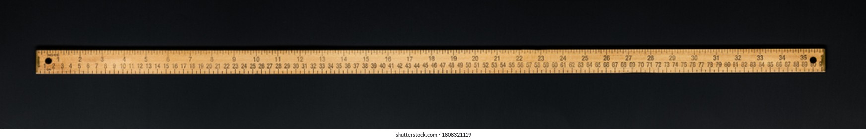 Wooden yardstick on black backgrounds whit centimeters and inches fractions scales.