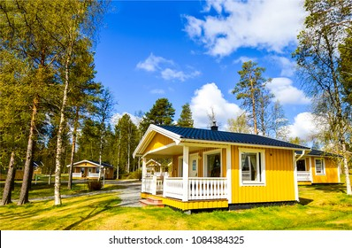 Wooden yellow house in forest camping landscape. Finnish yellow house in forest camp