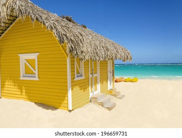 Wooden yellow hut on the beach covered with thatch against colorful kayaks, blue sky and azure water, Caribbean Islands