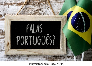 a wooden-framed chalkboard with the question falas portuges? do you speak Portuguese? written in Portugese, and some flags of Brazil against a rustic wooden background