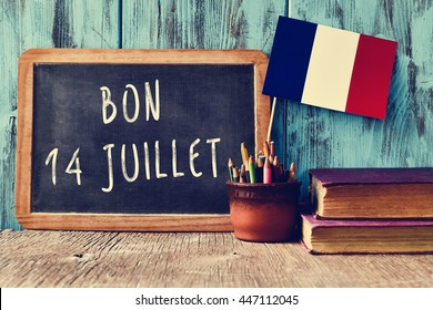a wooden-framed chalkboard with the text bon 14 juillet, happy 14th of July, the National Day of France, written in French and a flag of France, against a rustic blue wooden background