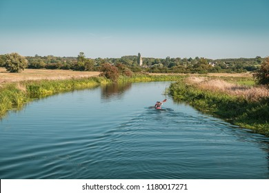 WOODFORD, NORTHAMPTONSHIRE,ENGLAND - 2nd SEPTEMBER 2018. Two canoeists in a double kayak paddle along the River Nene near Woodford Lock in Northamptonshire with Denford church in the distance