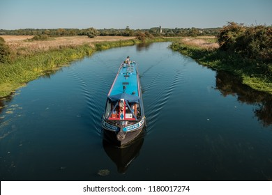 WOODFORD, NORTHAMPTONSHIRE,ENGLAND - 2nd SEPTEMBER 2018. Narrow boat passes along a calm River Nene near Woodford Lock in Northamptonshire with Denford church in the distance on a bright sunny day