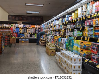 Woodinville, WA / USA - circa April 2020: Female worker restocking the beer cooler in a Haggen Northwest Fresh grocery store.