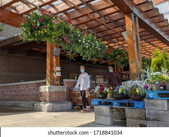 Woodinville, WA / USA - circa April 2020: View of a woman and man wearing face masks while shopping at a Haggen Northwest Fresh grocery store in the gardening section