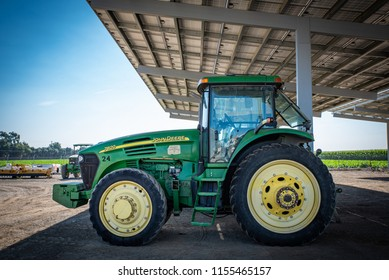 WOODLAND, CALIFORNIA/U.S.A. - JULY 19, 2018: A photo of a John Deere tractor under cover on a farm in California's Central Valley.