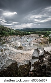 Woodland devastated by stone mining with clouds and sun rays. I foreground pieces of stone blocks. In middle/back ground landscape destroyed by mining and in contrast the green forests and meadows.