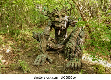 Woodland greenman sculpture setting in forest dappled with sun and shade at Renassiance Festival Muskogee Oklahoma USA 5 21 2016