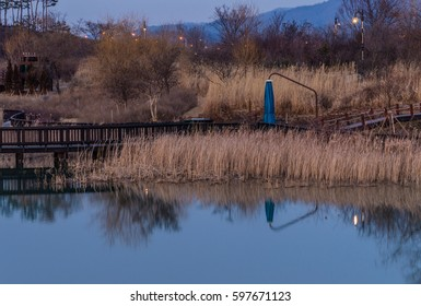 Woodland park with pond with smooth surface and trees and mountains in the background and pole lights illuminated and a wooden structure that says A place with a nice view in both English and Korean