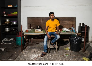 Woodlands / Singapore - June 2nd 2019: A labourer taking a rest at his kitchen.