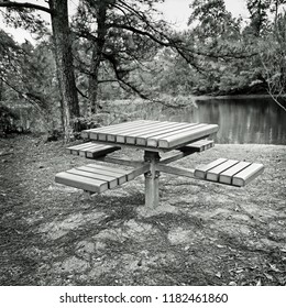 The Woodlands, TX USA - Feb 20, 2018  -  Picnic Bench by a Lake in B&W