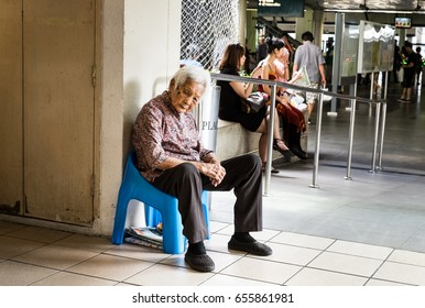 Woodlands/Singapore: 08th June 2017- An old lady is resting at the side of the walkway after collecting carton boxes.