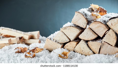 Woodpile with stacked logs and kindling buried in fresh winter snow in a close up view conceptual of natural biofuels for heating