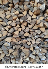 Woodpile. Wall firewood. Background from dry chopped logs in a heap. A wall of firewood, a background of dry chopped firewood. Alternative fuel concept. A snapshot of the natural background.