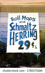 Woodridge, NY / USA - 06/16/2020: Vintage Grocery Store Sign Roll Mops and Schmaltz Herring 29 Cents per Lb circa 1950's, 1960's