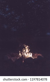 woods are burning in fireplace, warm, heat, fire in darkness. camping in nature in summer - vintage retro look