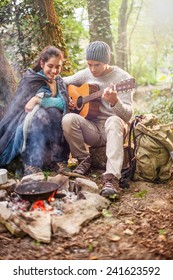 in the woods a couple sitting near a campfire, he plays guitar, she has a sleeping bag on the shoulders for warmth