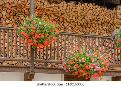 woodshed on  wooden balcony of traditional house covered with blossoming geranium flowers, shot on a bright summer day at Gressoney saint Jean,  Lys valley, Aosta, Italy