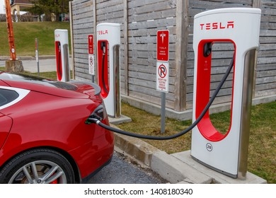 WOODSTOCK, CANADA - April 16th, 2019: Closeup of Red Tesla Model S charging at Tesla Supercharger, Woodstock, Ontario.