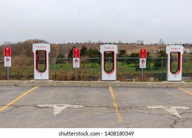 "WOODSTOCK, CANADA - April 16th, 2019: Tesla Supercharger stalls and designated parked marked with Tesla ""T"" emblem."