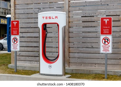 WOODSTOCK, CANADA - April 16th, 2019: Tesla Supercharger Stall with information/restrictions signs beside.