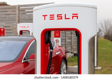 WOODSTOCK, CANADA - April 16th, 2019: Tesla Supercharger Stall with Tesla Model S charging in background.