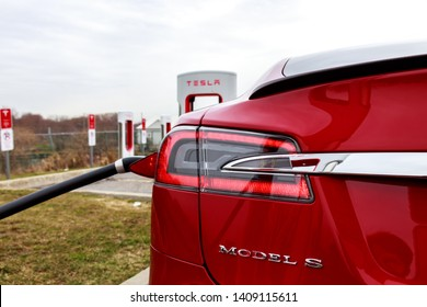 WOODSTOCK, CANADA - April 16th, 2019: Model S badge on supercharging Red Tesla Model S.