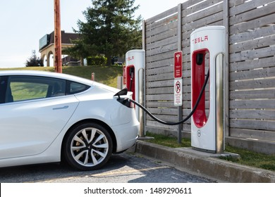 WOODSTOCK, CANADA - August 20, 2019: White Tesla Model 3 seen plugged-in at Tesla Supercharger Station.