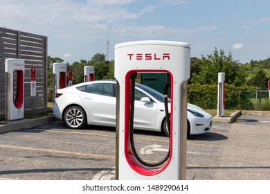 WOODSTOCK, CANADA - August 20, 2019: Tesla Supercharger Stall in-front of plugged-in white Tesla Model 3.