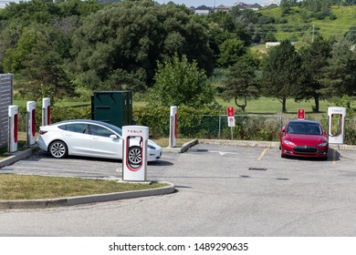 WOODSTOCK, CANADA - August 20, 2019: Tesla Supercharger Station seen while a white Tesla Model 3 and a Red Tesla Model S are parked and charging.