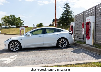 WOODSTOCK, CANADA - August 20, 2019: Full-view of white Tesla Model 3 parked and charging at Tesla Supercharger.