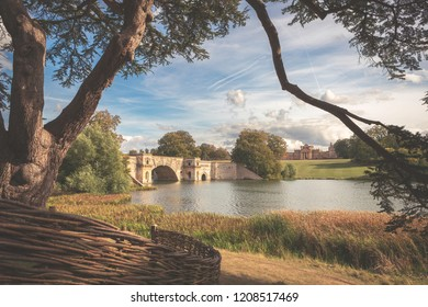 Woodstock, England, 09/15/2018: Beautiful bridge and lake with the famous Blenheim Palace in the background