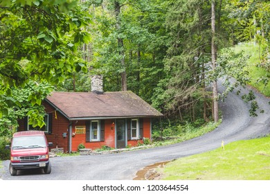Woodstock, New York / USA - 10 1 2018: legendary Woodstock village, country road cross river, lonely red wooden cabin and old van near.