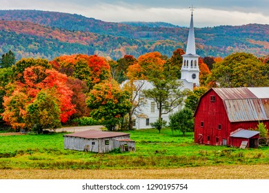 Woodstock, Vermont - October 8, 2018 - Red barn and church next to a harvested cornfiield with the Autumn colors in the background