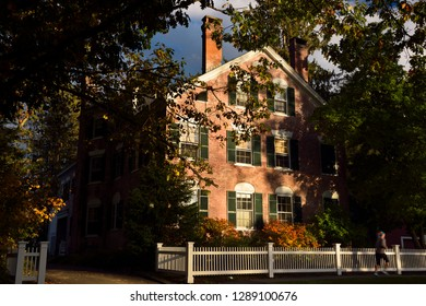 Woodstock, Vermont, United States - October 11, 2014: Historic red brick mansion with evening sun and jogger in Woodstock Vermont in the Fall