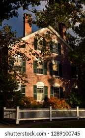 Woodstock, Vermont, United States - October 11, 2014: Historic red brick house with evening sun in Woodstock Vermont in the Fall