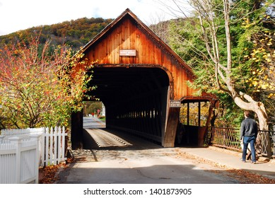 Woodstock, VT, USA October 10, 2012 A young man walks towards a covered bridge on a fall day in Woodstock, Vermont