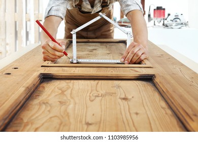 woodwork concept, carpenter with the meter makes the shape of a house
