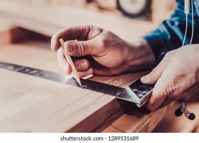 Woodwork and furniture making concept. Carpenter in the workshop marks out the details of the furniture cabinet using a setsquare close up view