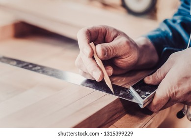 Woodwork and furniture making concept. Carpenter in the workshop marks out the details of the furniture cabinet using a setsquare close up