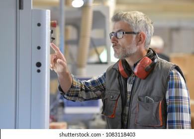Woodwork technician programming sawmill machine