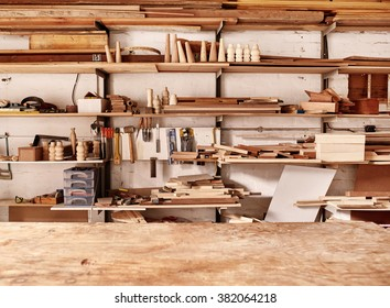 Woodwork workshop wall with many shelves holding a variety of wooden pieces and planks of wood, and some hand tools, with a wooden work bench in the foreground