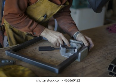 Woodworker adjusts metal framing for stool seat.